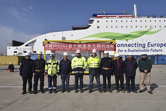 Some members of the project team stand infront of the first cabin unit to be fitted to STENA ESTRID prior to it being hoisted onto the vessel. AVIC Weihai.