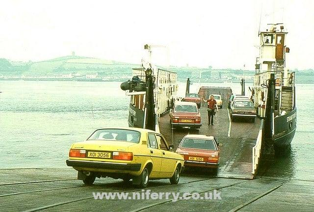 "The ""Strangford Ferry"" loading at Strangford for Portaferry. The car nearest the camera is a Morris Marina while a Ford Cortina is on the ramp. A Mini is visible behind the member of the crew directing the vehicles. Taken in 1981. Photo © Albert Bridge (cc-by-sa/2.0)"